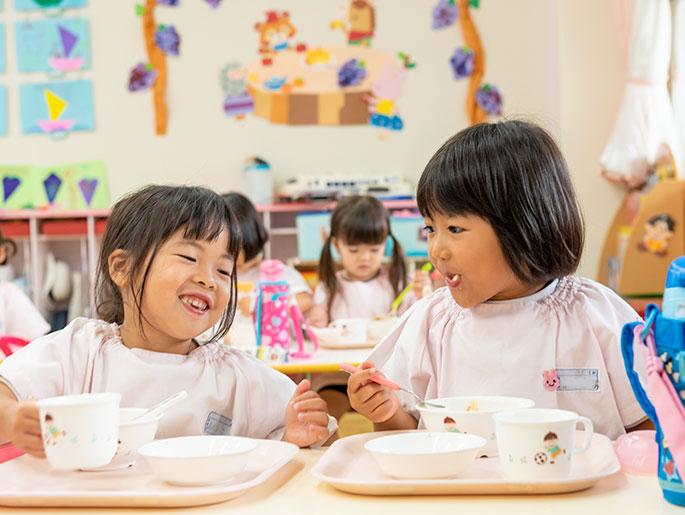 友達と楽しく食事する園児