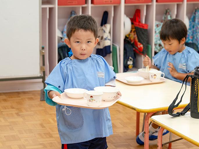 食器を片付ける園児