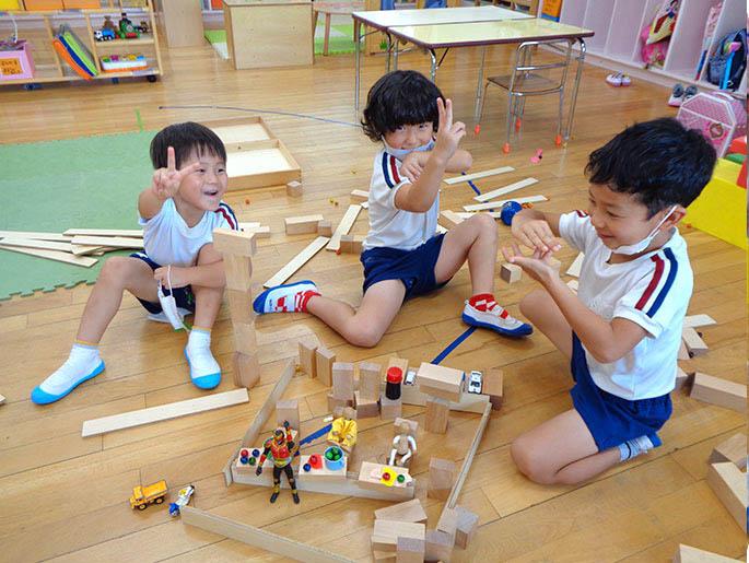 積み木とフィギュアで遊ぶ園児