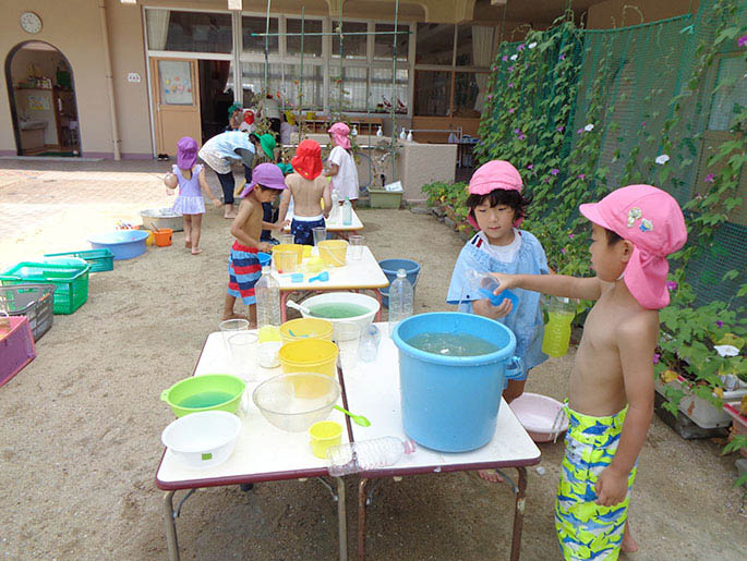 水に色を付けて遊ぶ園児