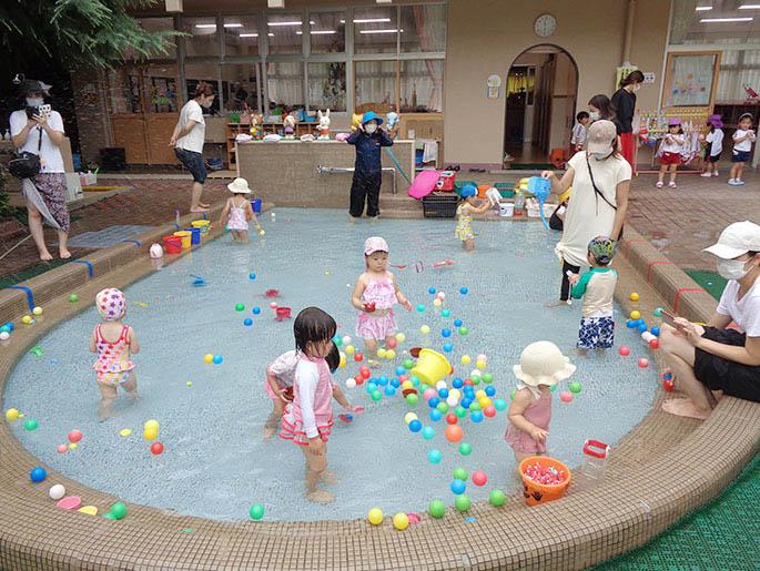 プールで遊ぶ園児とそれを見守る保護者